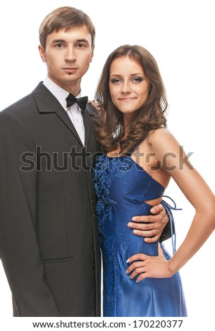 Young beautiful elegant couple - man in suit and bow tie with woman in blue dress.
