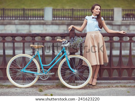 Young beautiful, elegantly dressed woman with bicycle. Beauty, fashion and lifestyle - stock photo