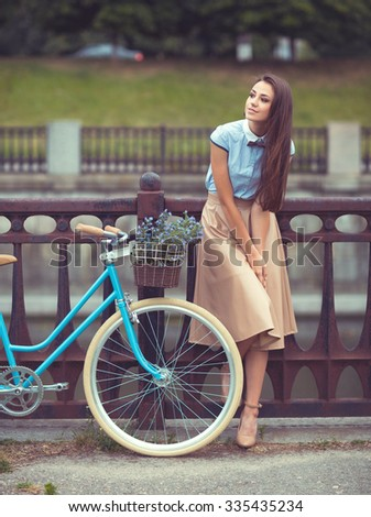 Young beautiful, elegantly dressed woman with bicycle outdoor. Beauty, fashion and lifestyle
