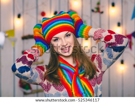 Young beautiful european girl in colored knitted hat and gloves. Woman smiling, standing on the background of Christmas decorations.