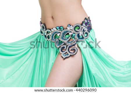Young beautiful exotic eastern women performs belly dance in ethnic green dress. Isolated on white background. Studio shot - stock photo