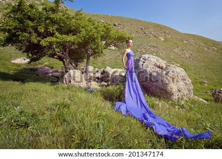 Young beautiful fairy woman at the mountain background. - stock photo