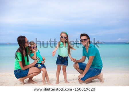 Young beautiful family of four enjoyed relaxing on the beach