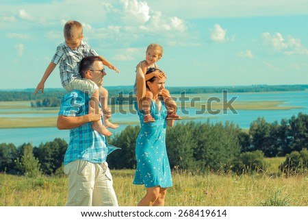young beautiful family of four on the background of the open landscape - stock photo