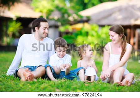 Young beautiful family of four sitting on grass