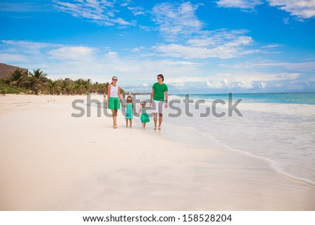 Young beautiful family of four walking on the white sandy beach - stock photo