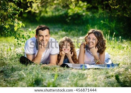 Young beautiful family of three having fun together outdoor. They are lying on a lawn look happy and smile. Fun outside sunny day.