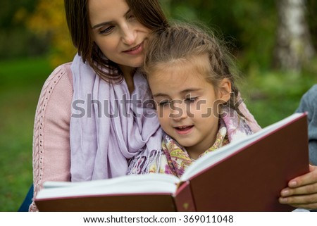 Young beautiful family sitting on the green grass in the park with big book. Reading fairy tale and smiling. Happy healthy family. - stock photo