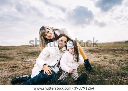 Young beautiful family walks on autumn mountain terrain. mom and two daughters on a mountain cliff on the background of  mountains on a cloudy day. little douther sit in the earth