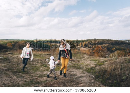 Young beautiful family walks on autumn mountain terrain. mom and two daughters on the background of  mountains on a cloudy day. They have fun and cuddling