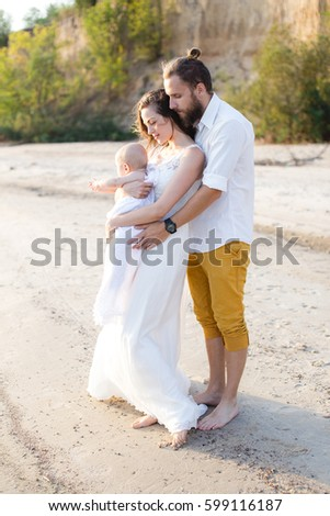 Young beautiful family with a child on the beach. Man and woman with baby happy in love relaxing on summer holidays. Travel vacation concept.