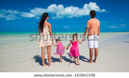 Young beautiful family with two daughters having fun at beach - stock photo