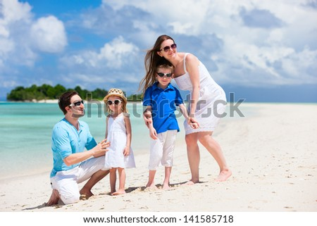 Young beautiful family with two kids on tropical vacation - stock photo