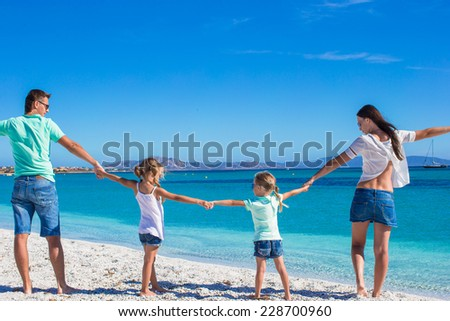 Young beautiful family with two kids on tropical vacation