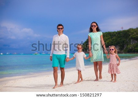 Young beautiful family with two kids walking on tropical vacation