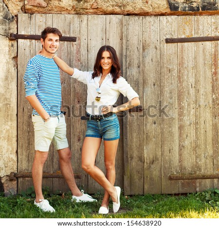 Young beautiful fashion couple in love having fun outdoor in summer. Man and his girlfriend standing near house and smiling.  - stock photo
