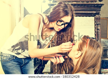Young beautiful fashion girl applying make-up by make-up artist  - stock photo
