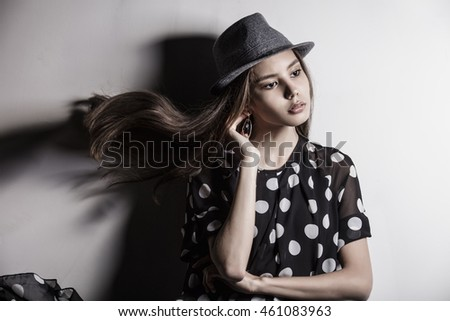 Young beautiful fashion model girl Asian girl with hat in the Studio