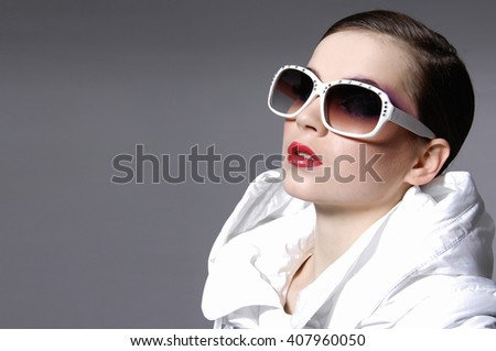 young beautiful fashion model in sunglasses on gray background - stock photo