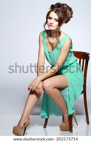 young beautiful fashion model sitting on a chair and looking at camera on gray background - stock photo