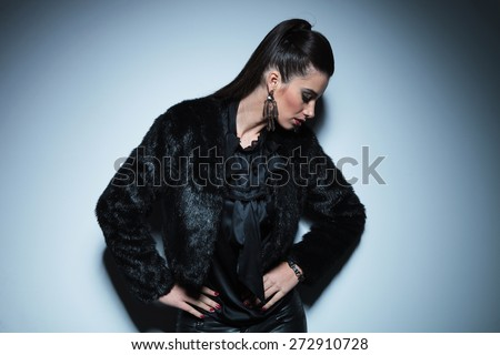 Young beautiful fashion woman looking down while holdinh her hands around the waist. - stock photo