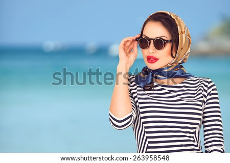 Young beautiful fashion woman portrait. Vintage stylish female in head scarf and sunglasses. Cruise traveling tourism concept. Blur blue ocean background with copy space  - stock photo