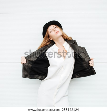 Young beautiful fashionable woman in leather jacket and white blouse posing outdoors against garage door - stock photo