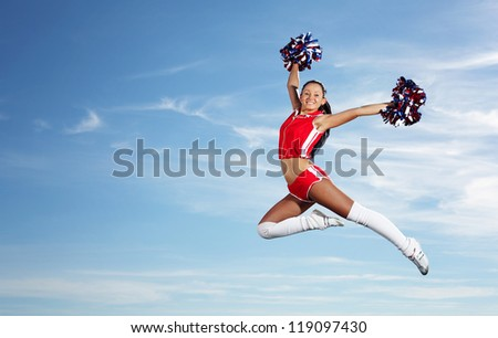 Young beautiful female cheerleader in uniform jumping high - stock photo