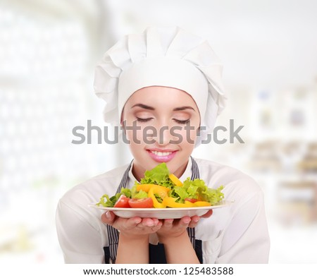 young beautiful female chef presenting food - stock photo