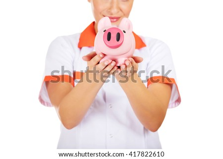 Young beautiful female doctor or nurse holding a piggybank - stock photo