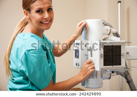 Young beautiful female doctor setting up x-ray machine. - stock photo