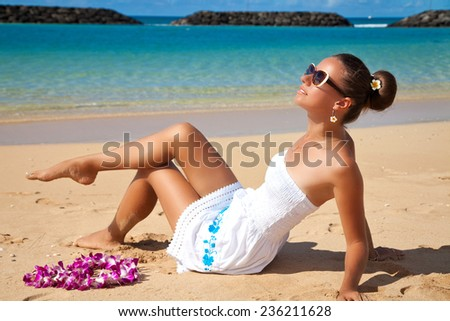 Young beautiful female enjoying sunny day on tropical beach. Summer luxury vacation in Hawaii. - stock photo