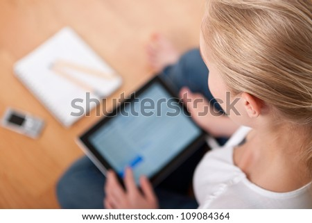 Young beautiful female female student using a tablet computer while studying and organizing her time (overshoulder, focused on head)