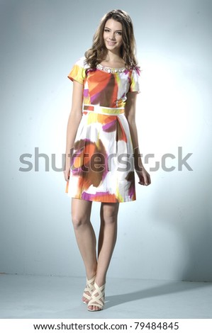 Young beautiful female model in colorful dress on light background - stock photo