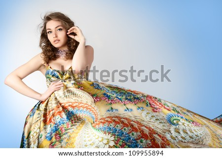 Young beautiful female model in colorful dress on light blue background. - stock photo