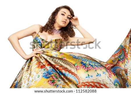 Young beautiful female model in colorful dress on white background.