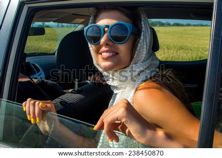 Young beautiful female model in sunglasses looks out the window of the white car. She travels on a background of yellow fields - stock photo
