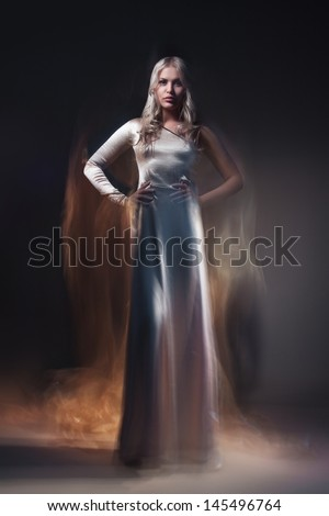 Young beautiful female model in white dress on black background