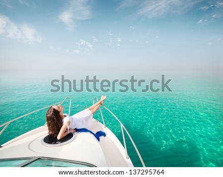 young beautiful female model lying on the deck of a yacht at sea. woman resting on the water - stock photo