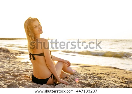 young beautiful female on beach enjoying vacation during sunset or sunrise