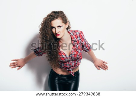 Young beautiful female on white background. She is very confident and sexy. She wearing leathers and plaid shirt/Young beautiful female - stock photo