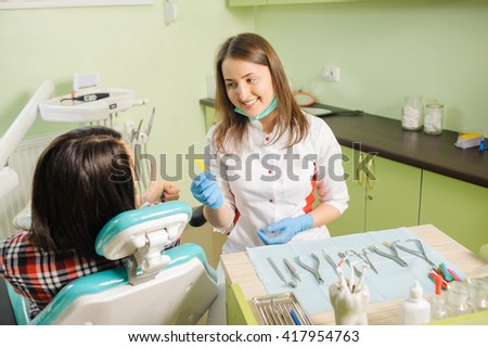 Young beautiful female orthodontist showing rubber draft of for braces to her female patient. Patient giving thumb up. Different dental instruments and tools for orthodontic treatment.