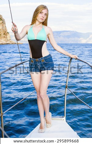 young beautiful female posing on a yacht in a sea - stock photo