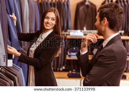 Young beautiful female shop assistant smiling and offering a suit to a modern young handsome businessman in the suit shop - stock photo