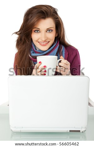 Young beautiful female sitting behind laptop, holding a cup smiling