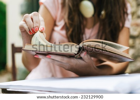 Young beautiful female sitting outside and studying hard. / Young woman doing homework on the home garden. - stock photo