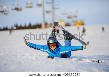 Young beautiful female skier in blue ski suit orange goggles and helmet lying on the snow and having fun at ski resort at Carpathian Mountains on a sunny day. Ski vacation. - stock photo