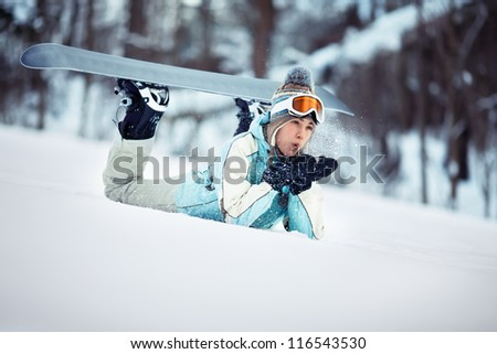 Young beautiful female snowboarder resting on ski slope, she's lying on front and blowing snow off her hands