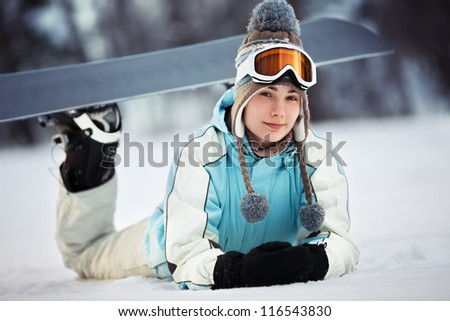 Young beautiful female snowboarder resting on ski slope, she's lying on front and smiling, close up - stock photo