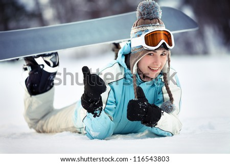 Young beautiful female snowboarder resting on ski slope, she's lying on front, showing thumbs up and smiling, close up